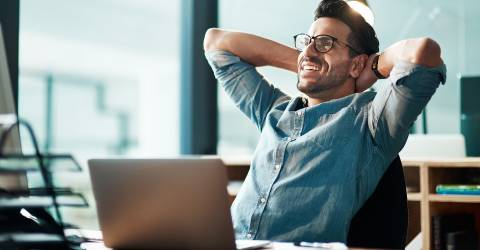 Zakenman leunt tevreden met een glimlach achterover op zijn stoel met zijn handen in zijn nek
